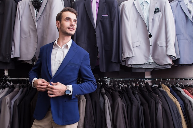 Homme élégant dans une boutique de vêtements sur le fond des vestes