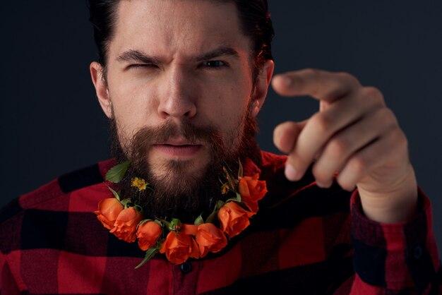 Un homme élégant dans une chemise à carreaux fleurs dans une barbe close-up fond sombre. photo de haute qualité