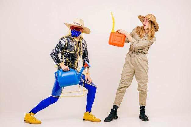 Homme élégant dans le masque et femme en chapeaux de paille posant avec arrosoir sur fond blanc