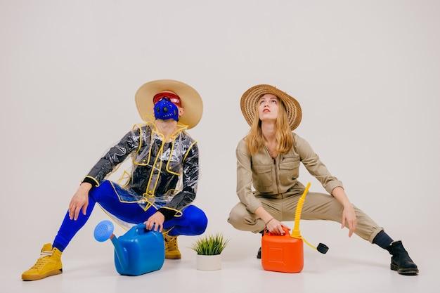 Homme élégant Dans Le Masque Et Femme En Chapeaux De Paille Posant Avec Arrosoir Sur Fond Blanc Photo Premium