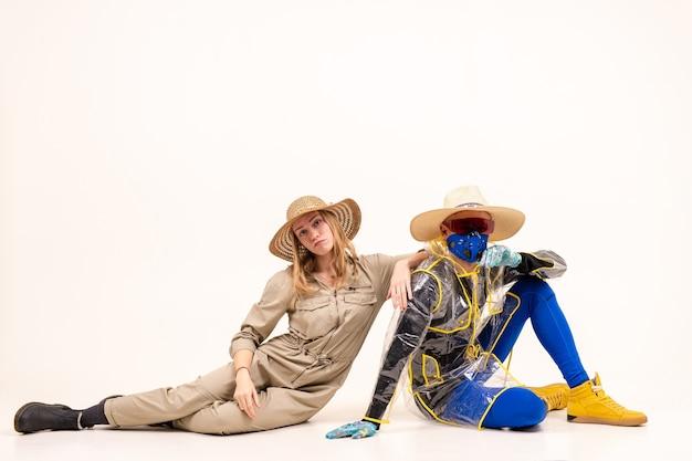 Homme élégant dans le masque et femme en chapeaux de paille posant sur fond blanc