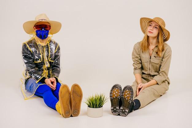 Homme élégant dans le masque et femme en chapeaux de paille posant avec de l'herbe dans le pot sur fond blanc