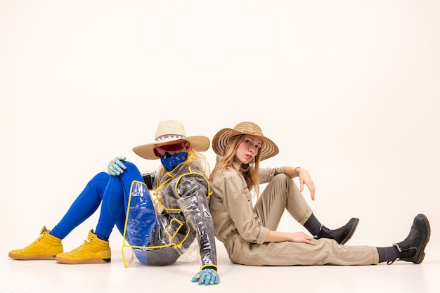 Homme élégant dans le masque et femme en chapeaux de paille posant sur un mur blanc