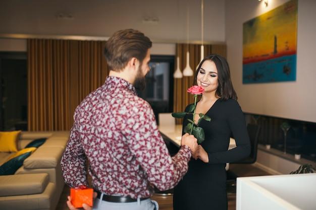 Homme élégant donnant rose à la femme