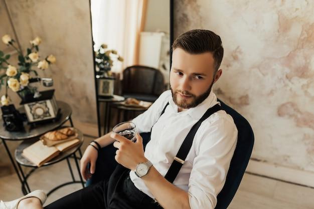 L'homme élégant est assis sur la chaise noire en studio et tient un verre de whisky.