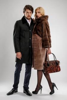 Homme élégant et femme glamour en manteau de fourrure posant avec tenue d'hiver.