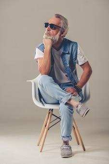 Homme élégant en jeans et lunettes de soleil