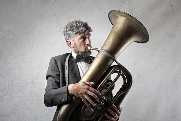 Homme élégant jouant sur un tuba