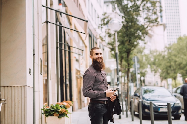 Homme élégant avec une longue barbe avec téléphone