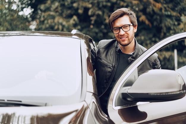 Homme élégant à lunettes est assis dans une voiture