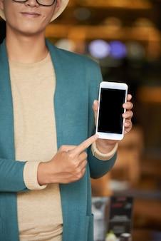 Homme élégant méconnaissable, debout dans un café, tenant un smartphone et pointant vers l'écran