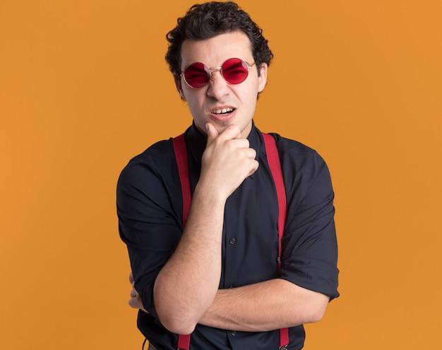 Homme élégant avec noeud papillon portant des lunettes et des bretelles à l'avant confondu avec la main sur son menton debout sur un mur orange