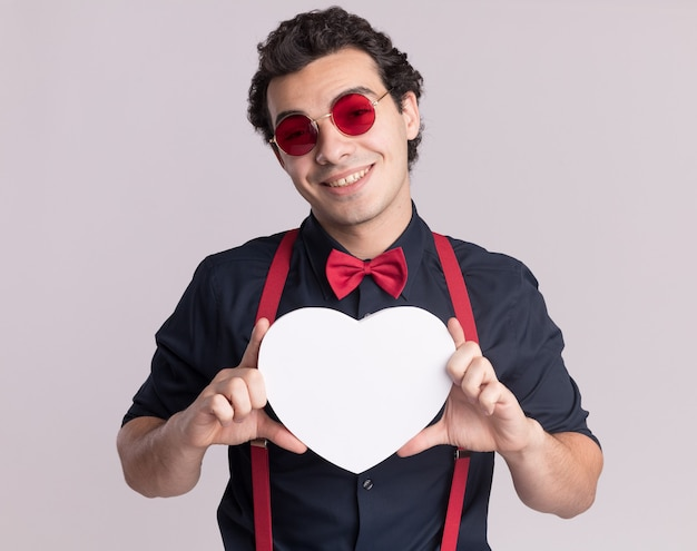 Homme élégant avec noeud papillon portant des lunettes et des bretelles tenant un coeur en carton à l'avant souriant joyeusement debout sur un mur blanc