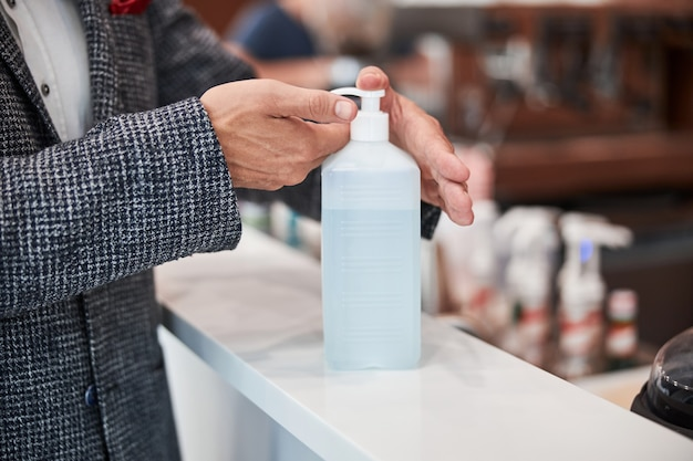 Un homme élégant pressant du désinfectant sur ses mains avant la désinfection