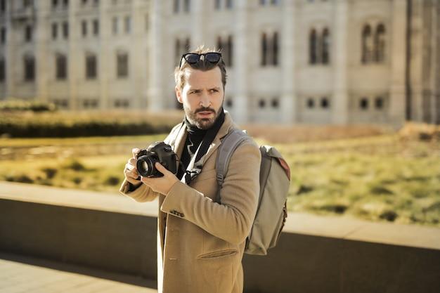 Homme élégant qui marche avec une caméra