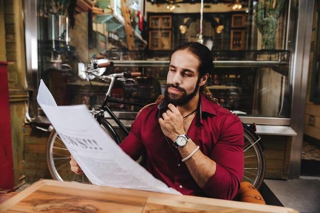 Homme élégant réfléchi tenant un journal tout en lisant les dernières nouvelles