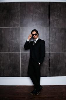 Homme élégant sérieux tenant des lunettes, photo pleine hauteur