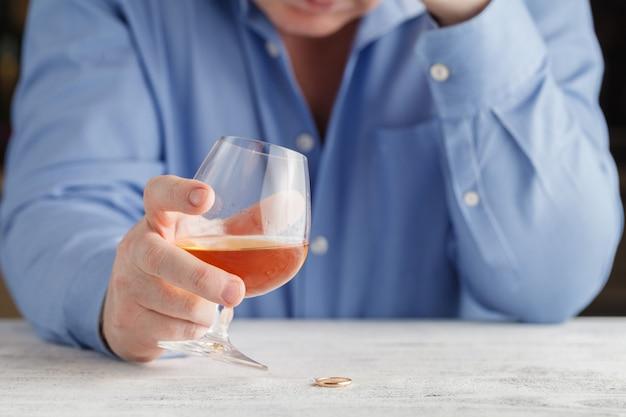 Homme élégant souffrant d'alcoolisme buvant du whisky