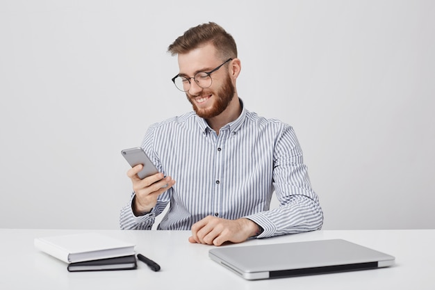 Un homme élégant et souriant a une expression heureuse et reçoit un message agréable