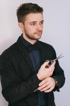 Homme élégant tient des ciseaux de coiffure dans sa main sur un fond blanc