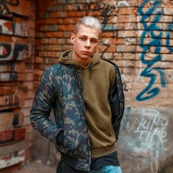 Homme élégant en vêtements de mode militaire près d'un mur avec du graphite