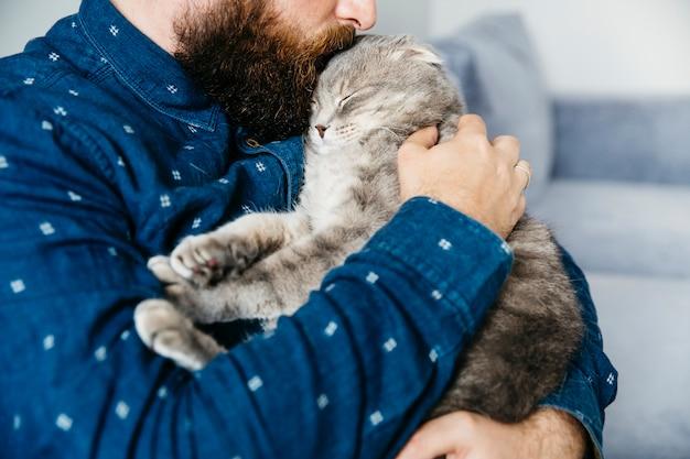 Homme embrassant un chat adorable
