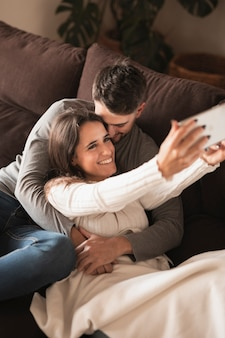 Homme embrassant une femme en prenant selfie