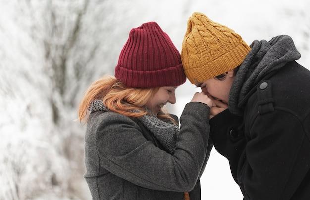 Homme embrassant les mains de sa petite amie
