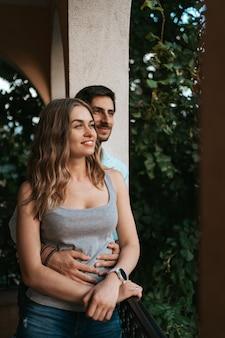 Homme embrassant sa femme au balcon. un couple détendu profite de la journée et de bonnes nouvelles. heureuse jeune famille