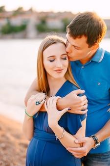 L'homme embrasse doucement souriant femme enceinte dans une robe bleue serrant ses épaules