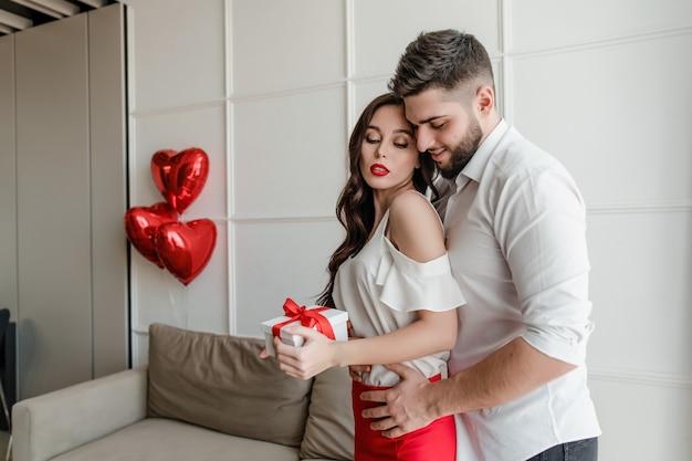 L'homme embrasse la femme avec un cadeau dans une boîte cadeau à la maison dans un appartement moderne