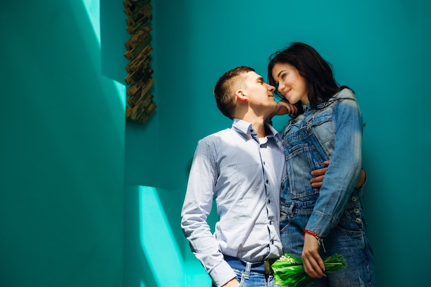 L'homme embrasse la femme et tient sa main dans sa poche. femme tient un bouquet de fleurs