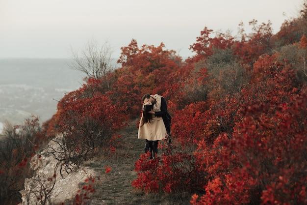L'homme embrasse passionnément sa petite amie sur le cou sur la forêt d'automne