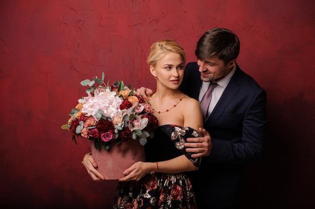 L'homme embrasse sa femme avec le bouquet de fleurs