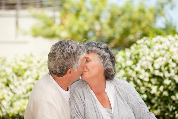 Homme embrasse sa femme dans le jardin