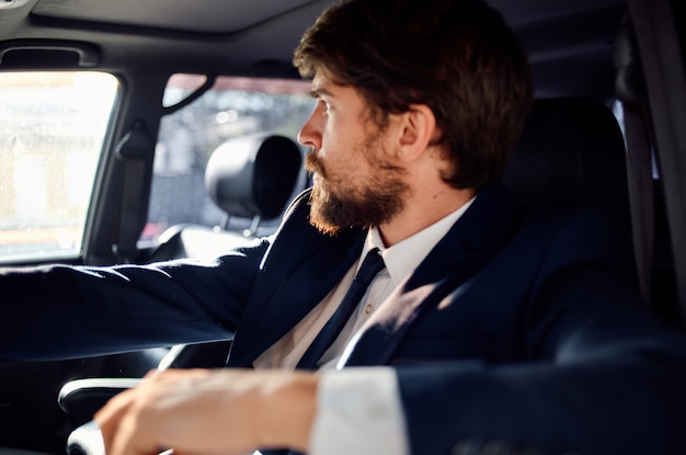 Homme émotif en costume dans une voiture un voyage pour travailler confiance en soi. photo de haute qualité