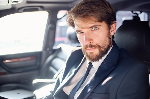 Homme émotif dans un costume dans une voiture un voyage pour travailler la confiance en soi. photo de haute qualité