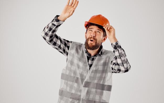Homme émotif dans le fond clair professionnel de construction de casque orange