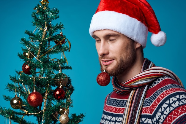 Homme émotif dans un santa hat décorations de noël vacances nouvel an fond rouge