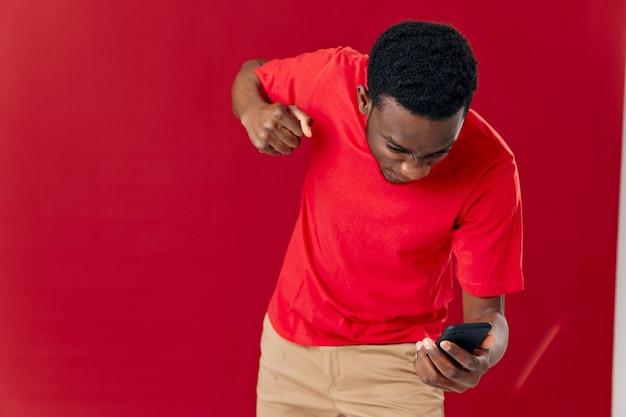 Homme émotif avec le téléphone dans l'insatisfaction de mains avec le studio de technologie