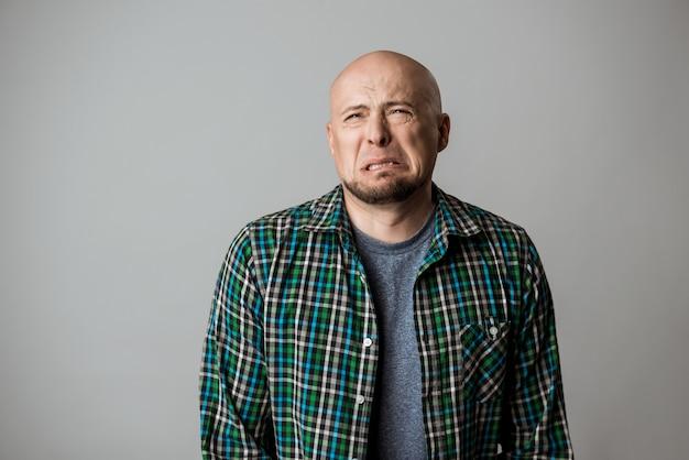 Homme émotif triste rancunier en chemise posant sur un mur beige