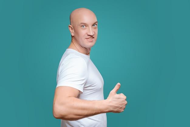 Un homme émotif vêtu d'un t-shirt blanc montre d'un geste de la main que tout est cool