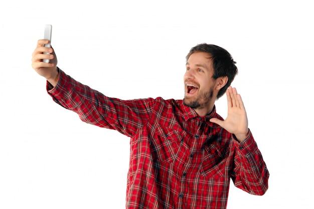 Homme émotionnel à l'aide de smartphone isolé sur studio blanc
