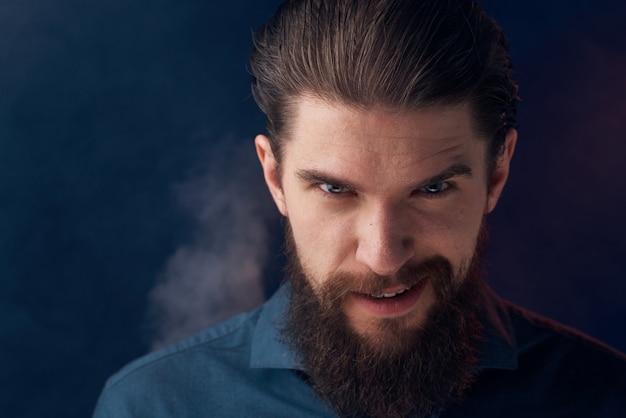 Homme émotionnel chemise noire look attrayant gros plan fumée en arrière-plan. photo de haute qualité