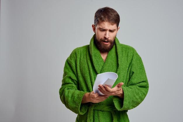 Homme émotionnel dans une robe verte avec une feuille de papier roulée dans les mains
