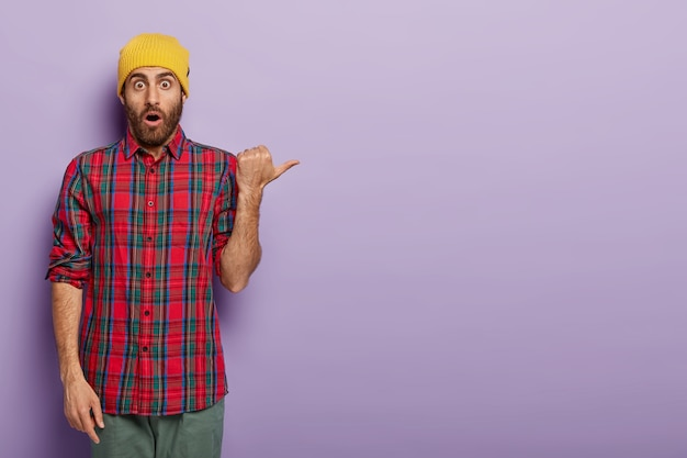 Un homme émotionnel effrayé pointe le pouce, porte un chapeau jaune et une chemise à carreaux, annonce quelque chose de cool