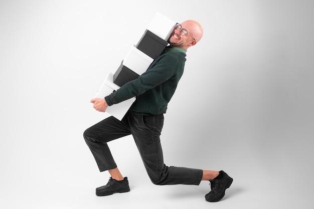 Homme émotionnel fatigué dans des vêtements élégants détient des boîtes de bureau