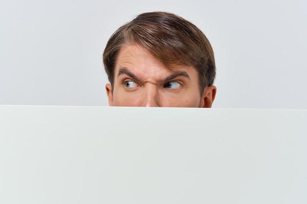 Homme émotionnel furtivement derrière une bannière publicitaire vue recadrée.