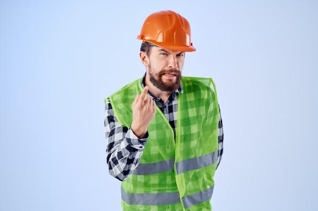 Homme émotionnel gilet vert casque orange flux de travail gestes de la main fond bleu