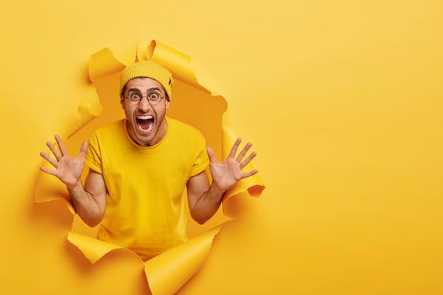 Homme émotionnel posant à travers du papier déchiré